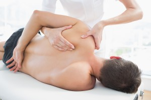 Professional female physiotherapist giving shoulder massage to m